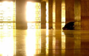 Man in sujud praying in a shinny masjid
